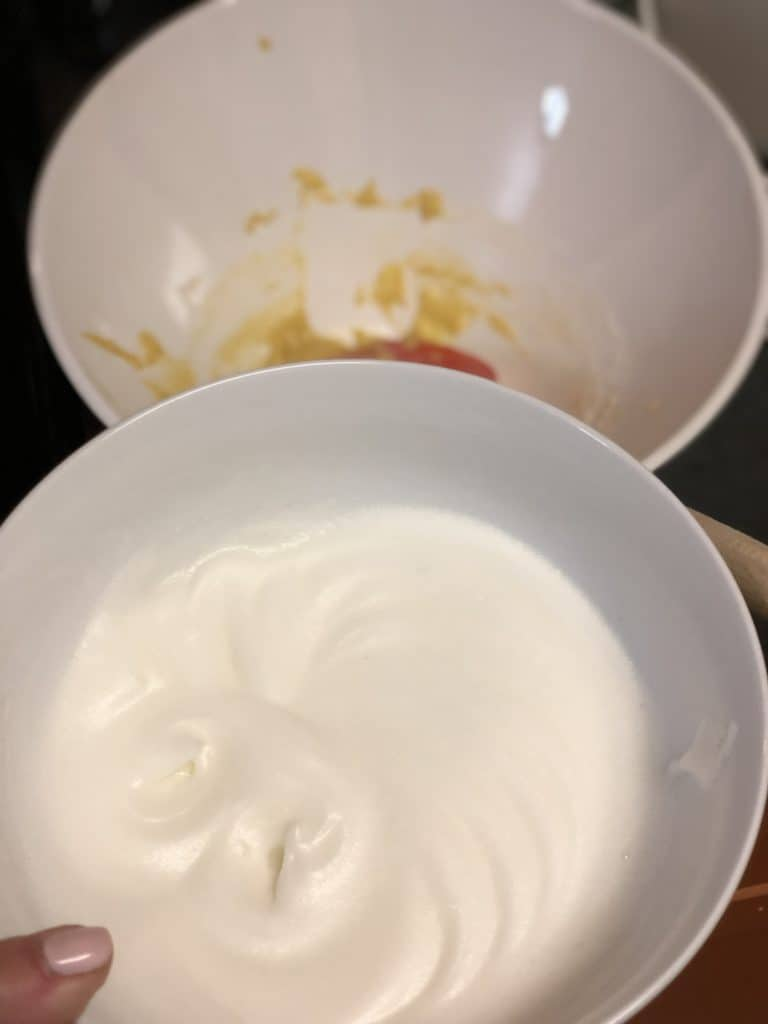 egg white foam in a white bowl