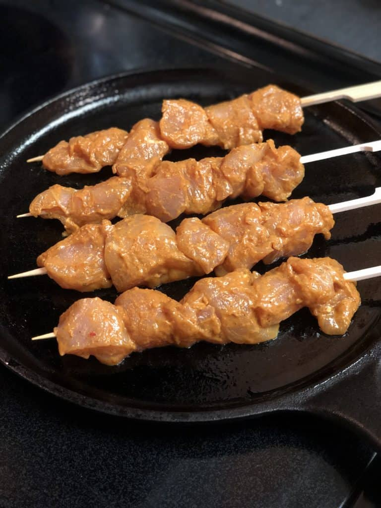 grilling chicken skewers for chicken satay