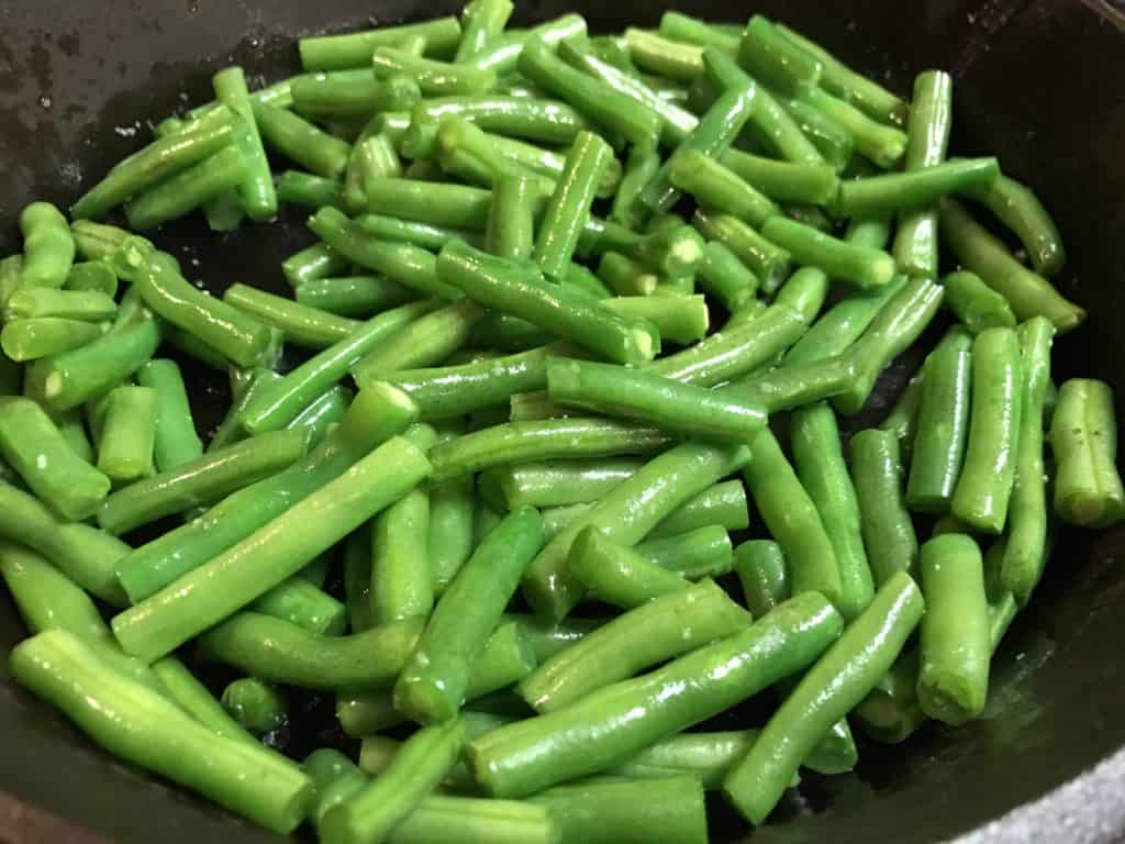 green beans searing in a cast iron pan