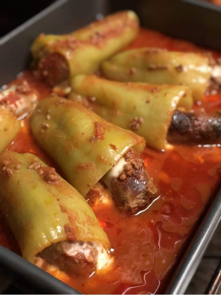 sausage stuffed peppers in a pan with sauce