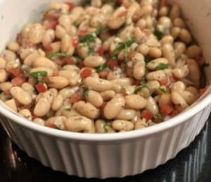a white bowl filled with Tuscan bean salad