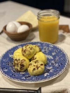 six sous vide egg bites sitting on a blue flowered plate with a glass of orange juice and a bowl of eggs in the background