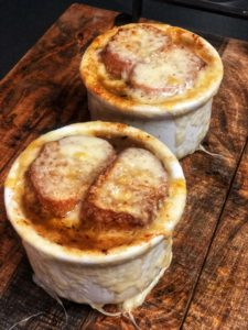 two bowls of french onion soup on a wooden board