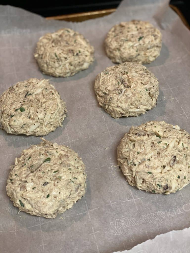 six crab cakes on a parchment paper lined baking sheet