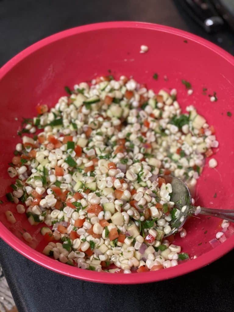 corn, red pepper, and parsley in a pink bowl