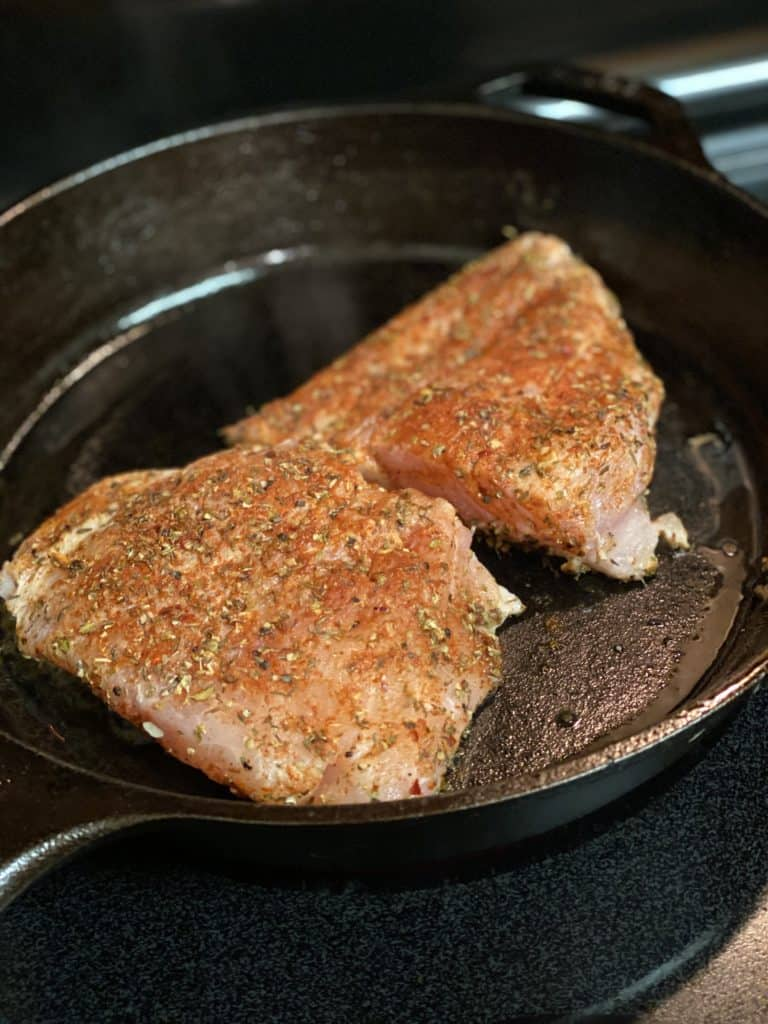 two pieces of blackened grouper in a cast iron pan