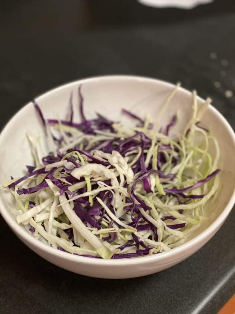 a white bowl of green and red shredded cabbage for cole slaw