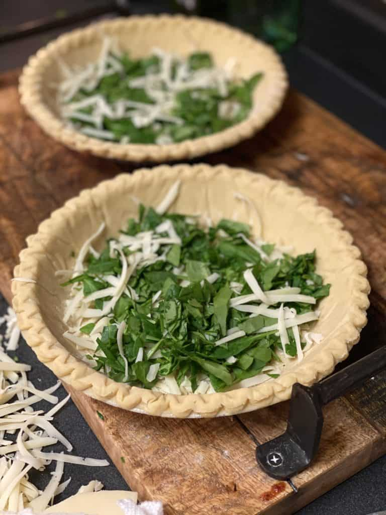 pie crust filled with Gruyere cheese and chopped spinach