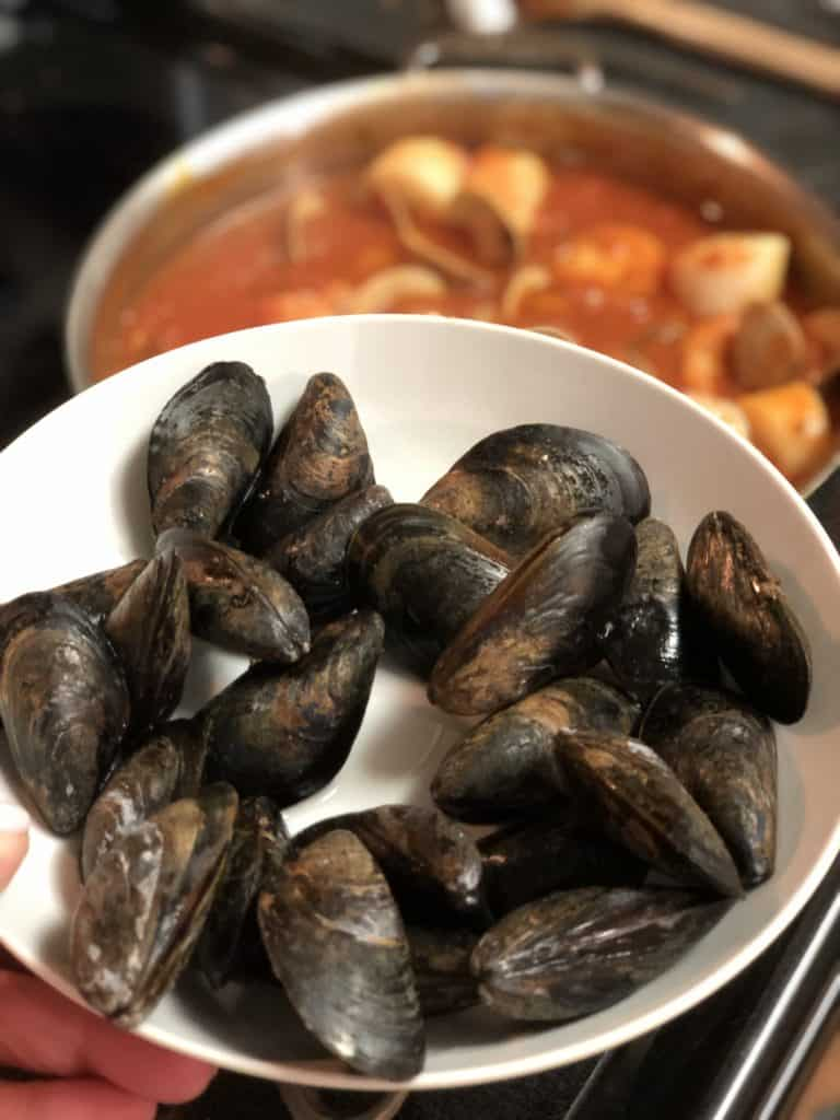 a white bowl of mussels