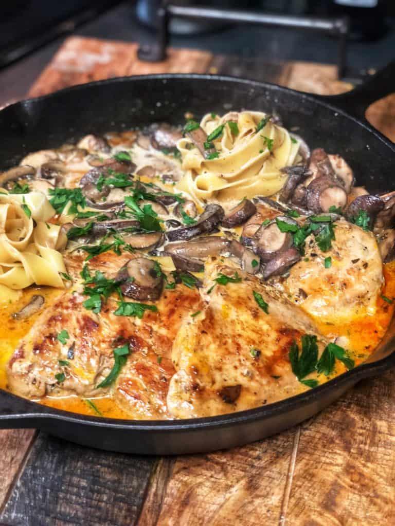 garlic mushroom chicken in a cast iron pan with pasta