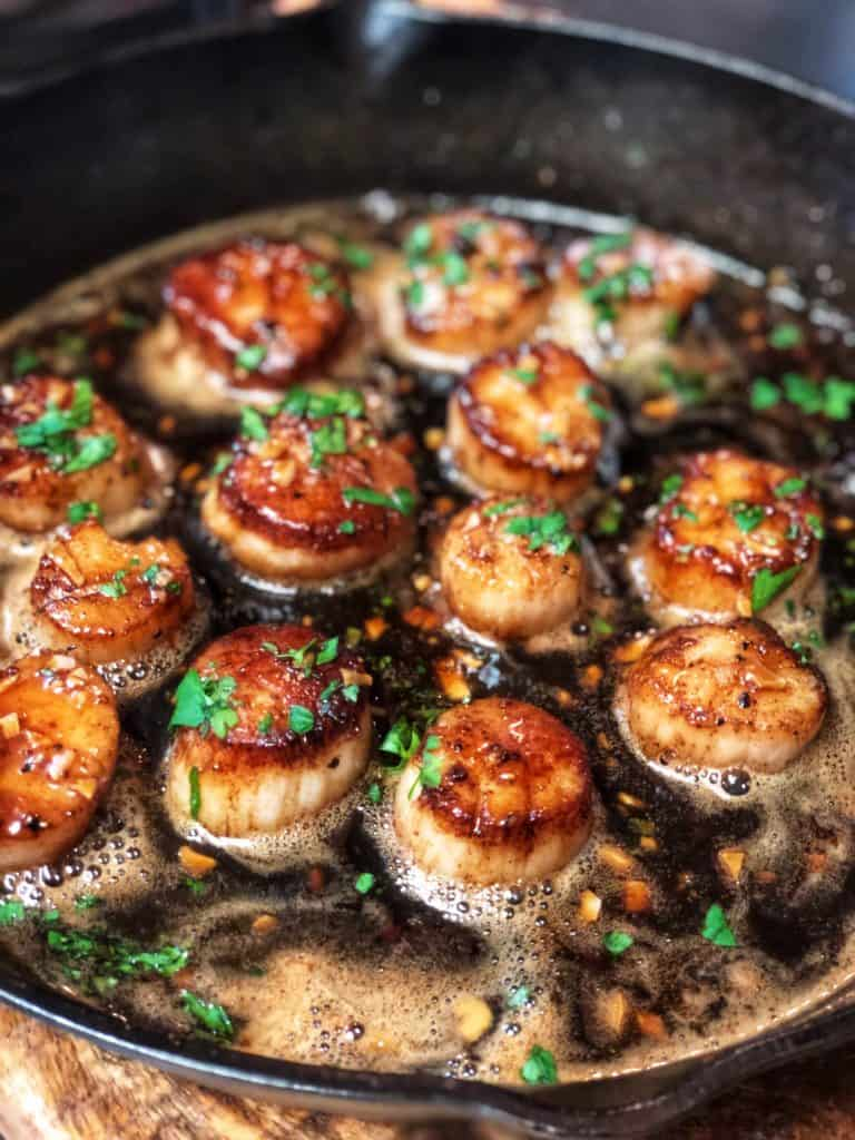 a cast iron pan of honey garlic scallops with brown butter