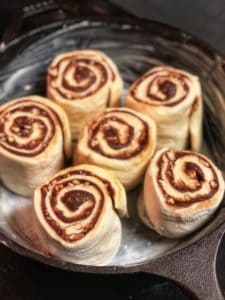 six cinnamon rolls in a cast iron pan ready to rise