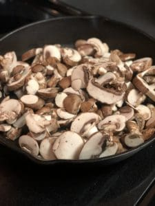 Sliced mushrooms cooking in cast iron pan