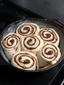 six cinnamon rolls ready to bake in a cast iron pan