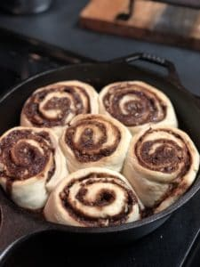 six cinnamon rolls baked in a cast iron pan