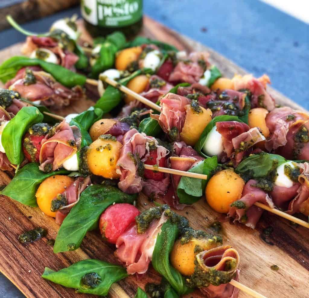 Prosciutto Melon Skewers with Basil Pesto on a wooden board