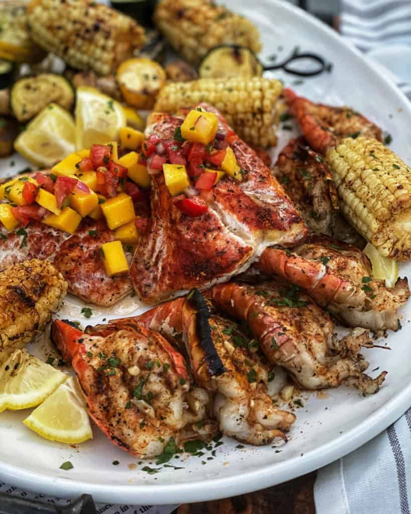 a plate of grilled grouper with mango salsa, shrimp, corn and vegetables