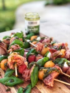 a wooden board of Prosciutto Melon Skewers with Basil Pesto