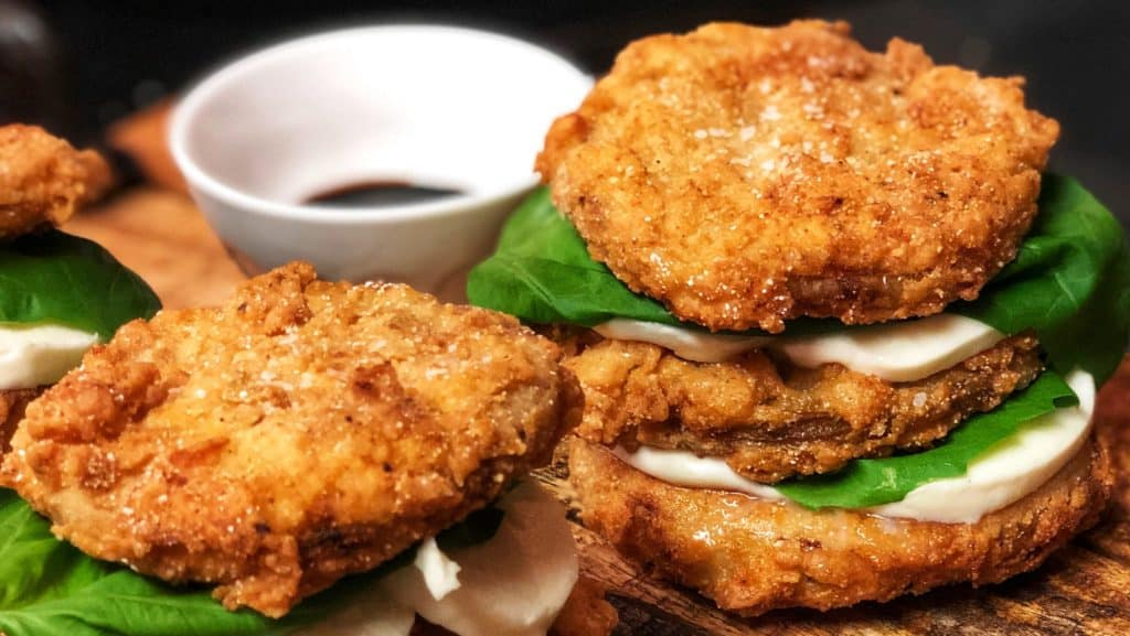 fried green tomato stacks on a wooden platter