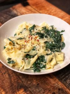 a white bowl filled with Spinach Ricotta Pasta