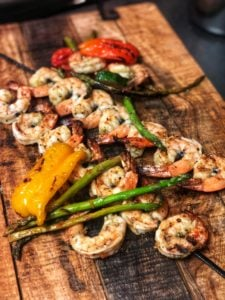 grilled shrimp and vegetables on a wooden platter for my orzo with pesto grilled shrimp
