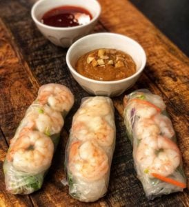 three shrimp spring rolls with cashew sauce on a wooden board