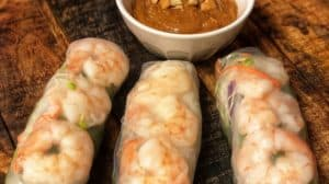 three shrimp rolls with a bowl of cashew dipping sauce