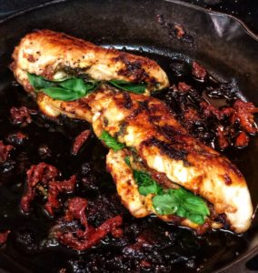 spinach and sun dried tomato pesto stuffed chicken in a cast iron pan
