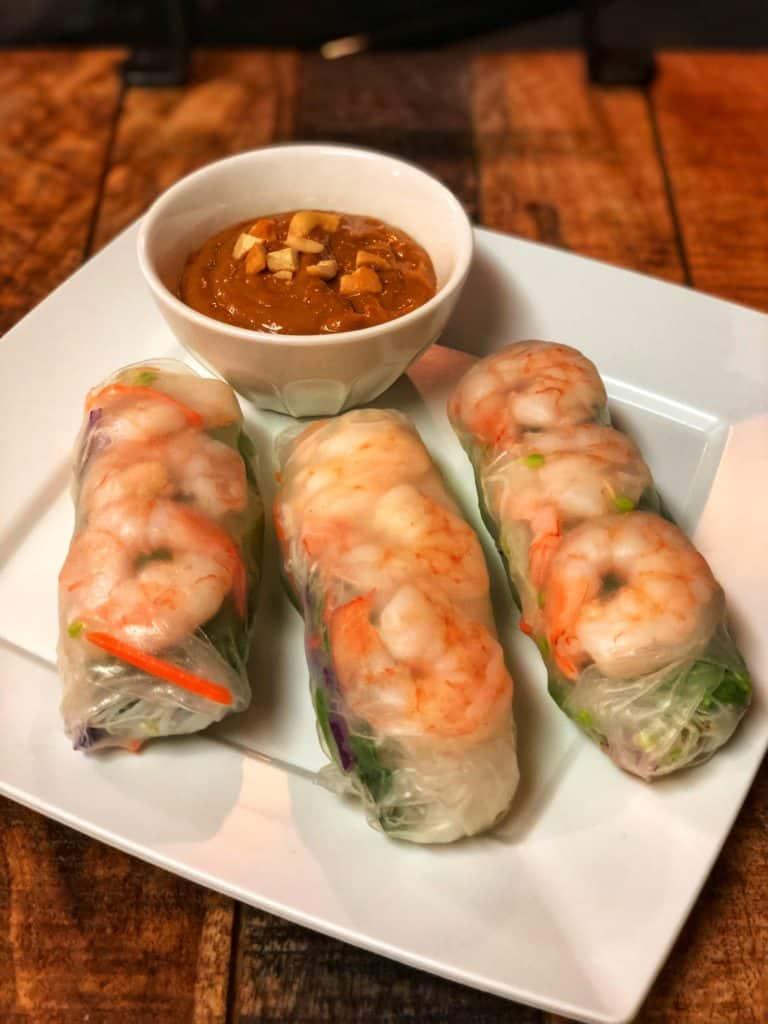 three shrimp spring rolls with cashew sauce
