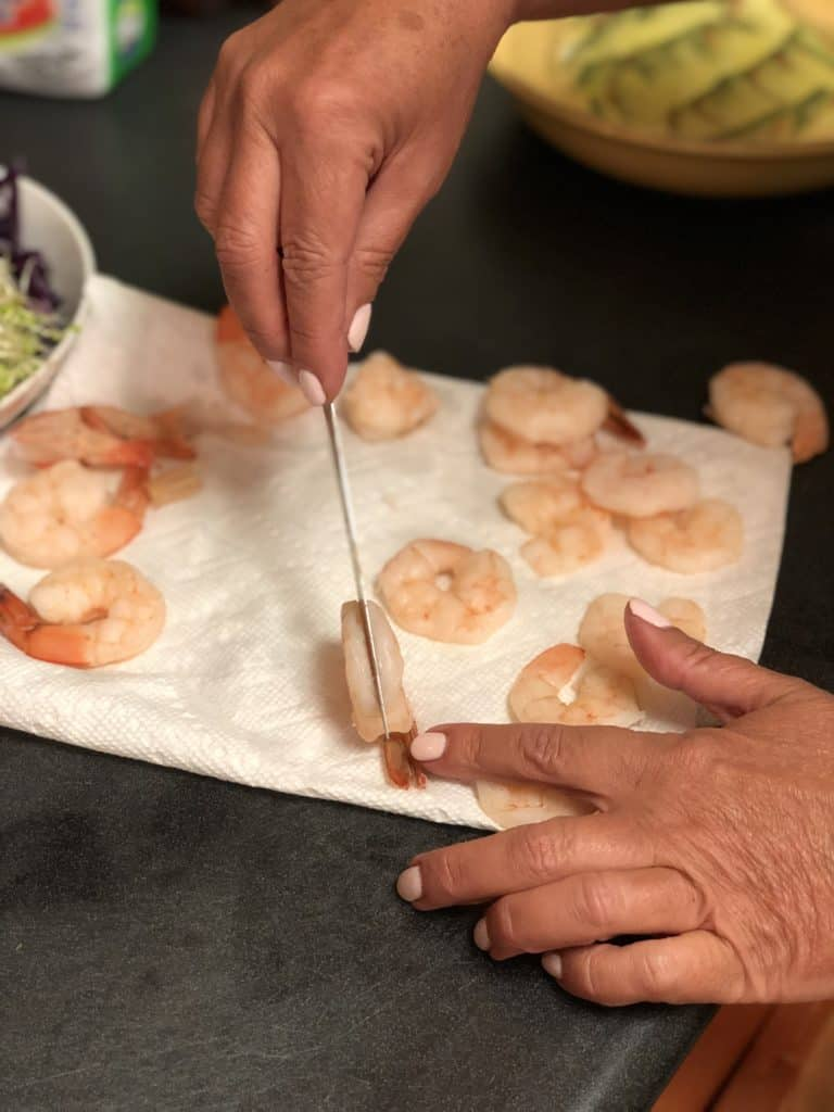 cutting poached shrimp in half