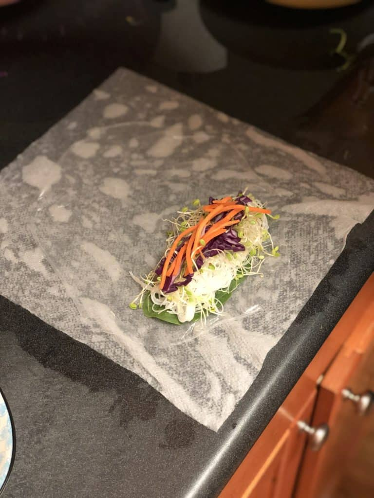 matchstick carrots placed on shrimp spring rolls with cashew sauce