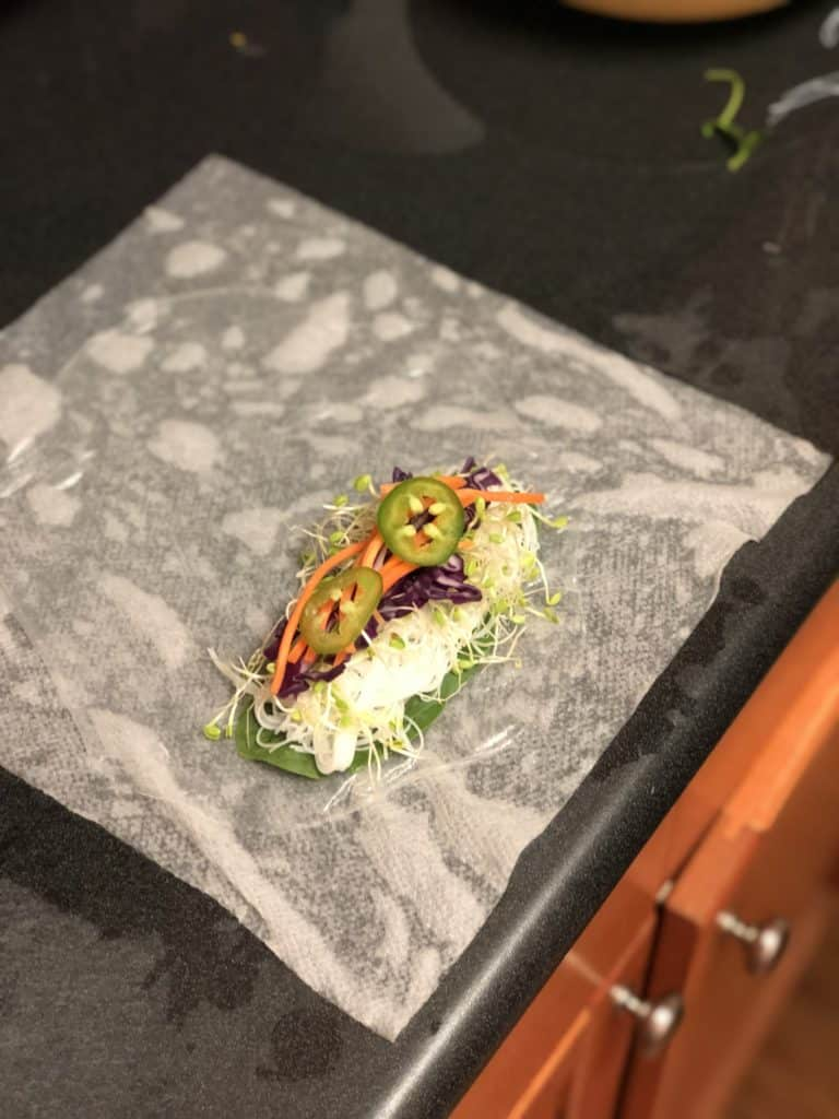 adding jalapeno slices to shrimp roll