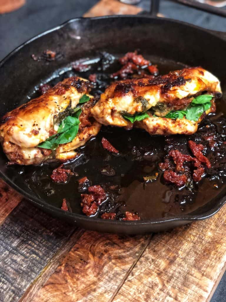 spinach and tomato pesto stuffed chicken in a cast iron pan