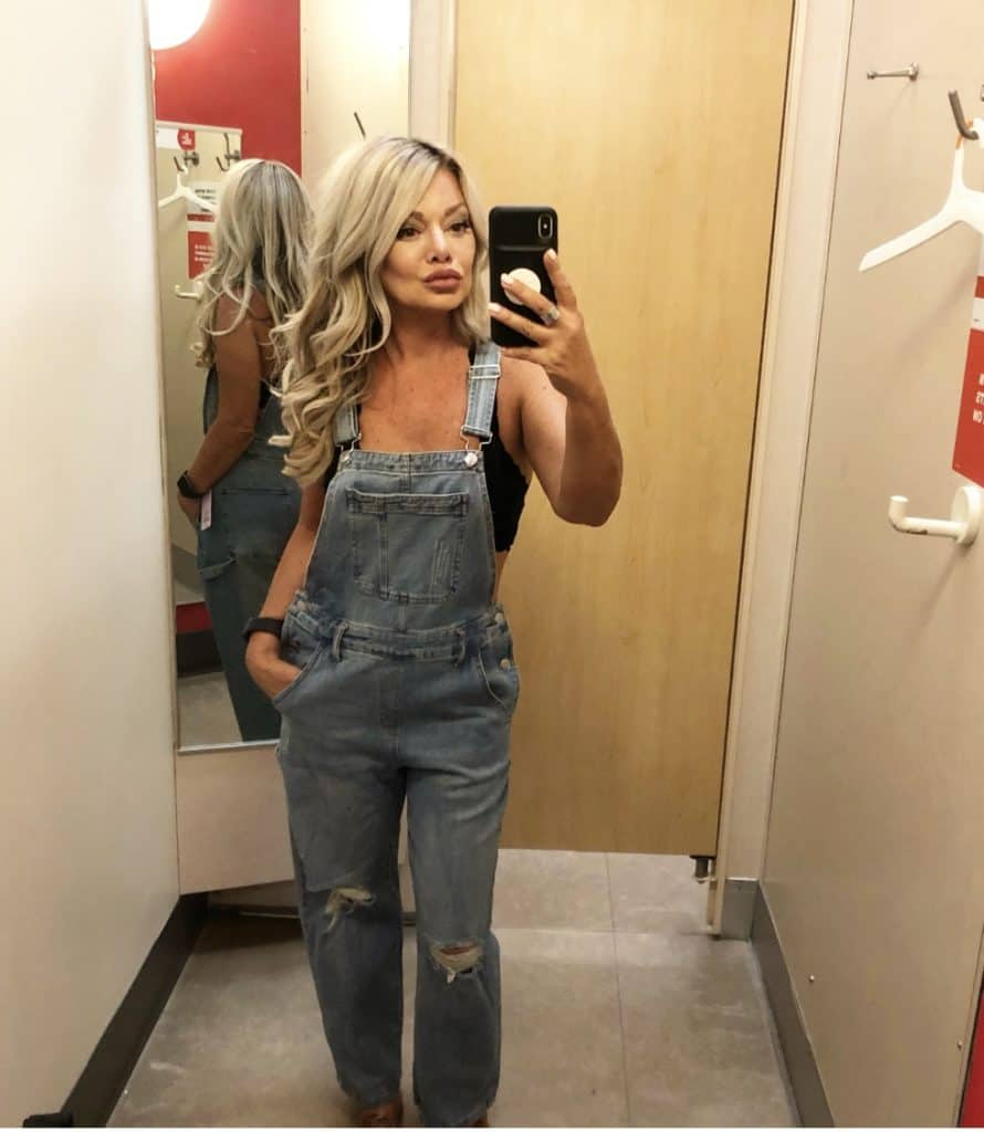 me taking a selfie in the target dressing room wearing overalls