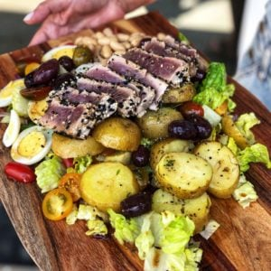 Nicoise Salad. Salad with Romaine, Potatoes, Olives, Hardboiled Eggs, Tomatoes, White Beans, and Seared Tuna