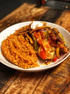 Chicken Fajita Casserole with Mexican Rice, crispy tortilla strips and sour cream