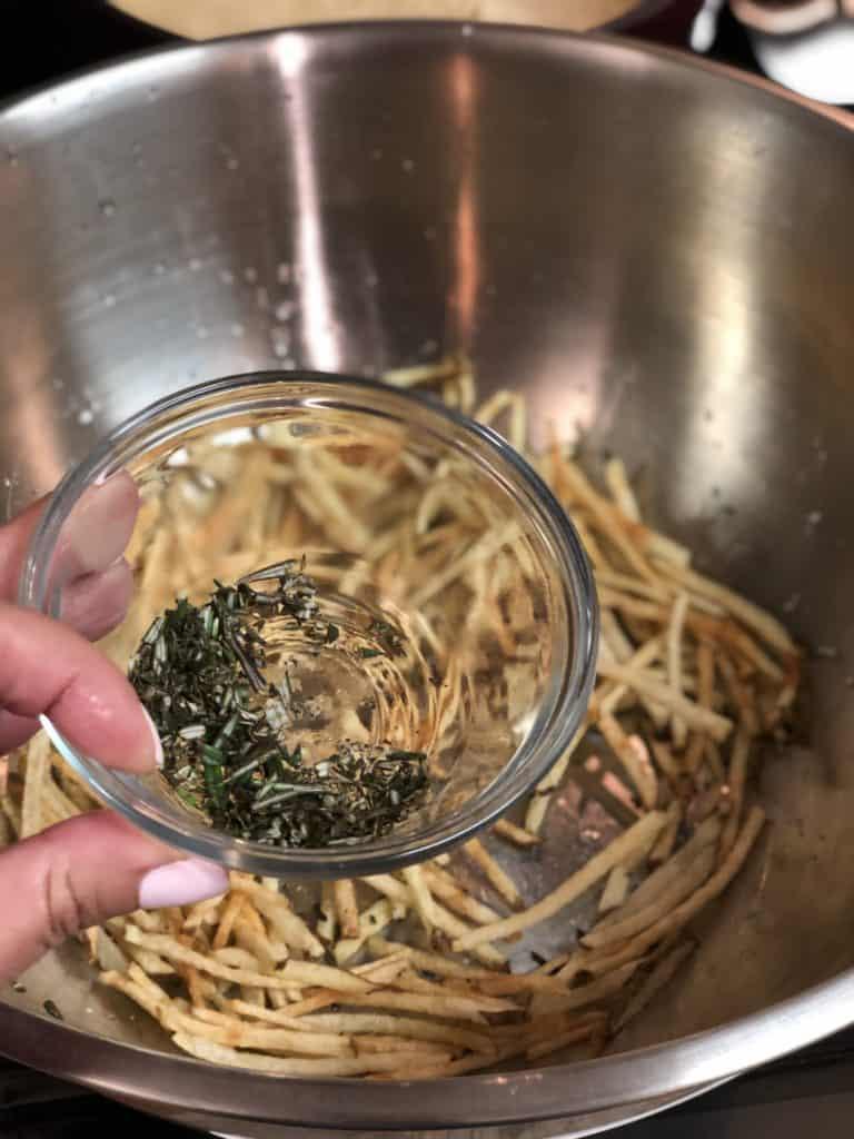 Adding fresh chopped rosemary to hot fries