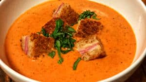 a bowl of Creamy Tomato Basil Soup garnished with fresh basil and Gruyere and Ham Croutons