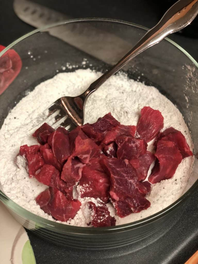 beef cubes in bowl of flour mixture