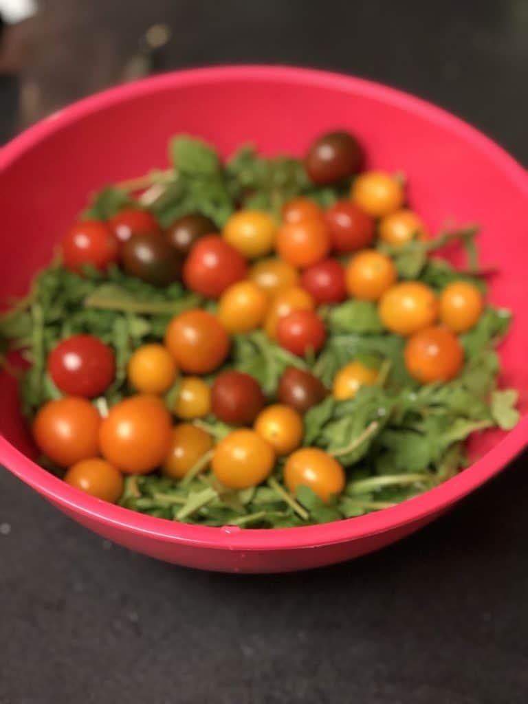 a bowl of arugula and tomatoes