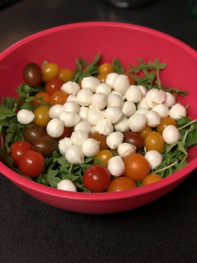 a bowl of arugula, tomatoes and mozzarella pearls