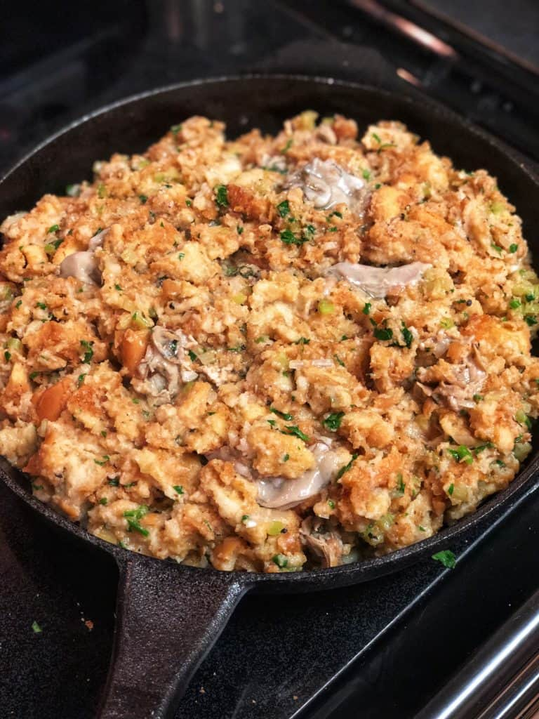 oyster dressing in a cast iron pan ready to bak