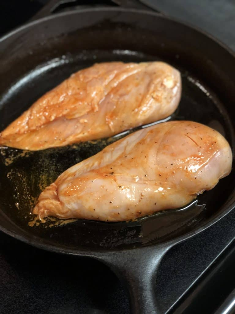 two boneless chicken breasts in a cast iron pan