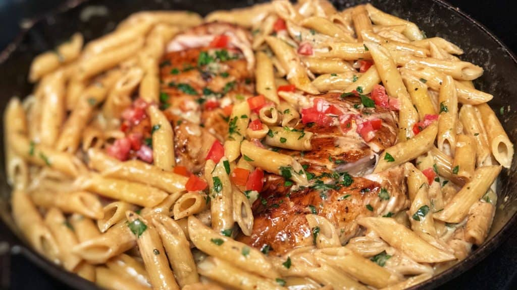 a cast iron pan full of cajun chicken pasta