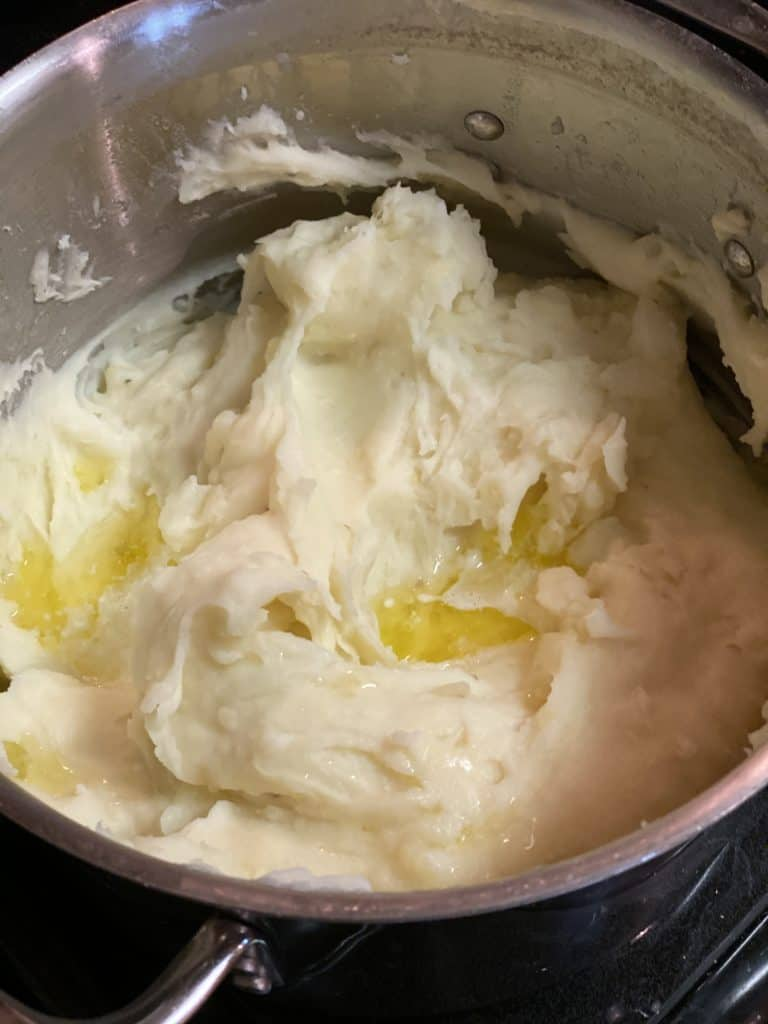 a pot of mashed potatoes topped with butter