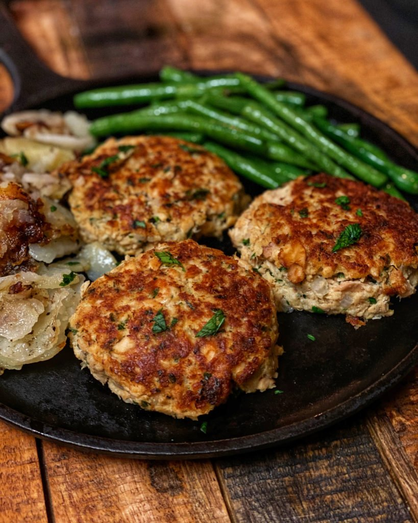Salmon patties on a plate with fried potatoes and fresh green beans
