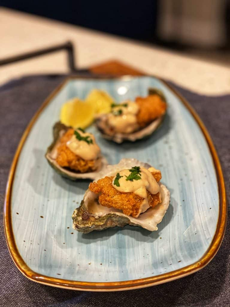 three southern fried oysters each sitting in half of an oyster shell topped with remoulade sauce on a blue plate