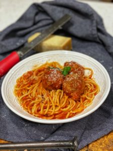 a white bowl of spaghetti with three meatballs on a blue napkin