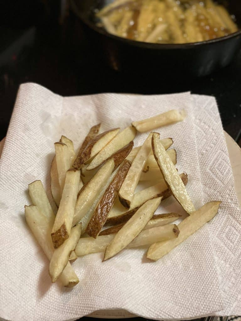 first fry of potatoes draining on paper towels
