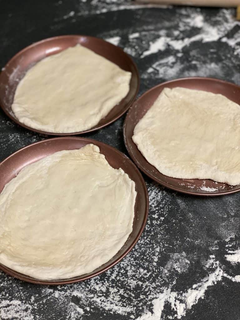 pizza dough formed in pans and brushed with olive oil for my prosciutto and fig pizza